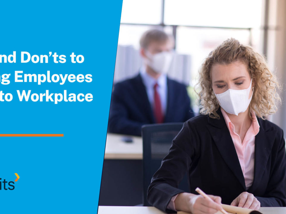 Employees sitting at desk working while wear masks